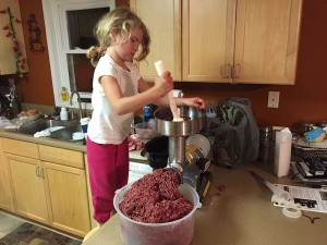 Jordyn Erdody grinding venison for homemade hot dogs